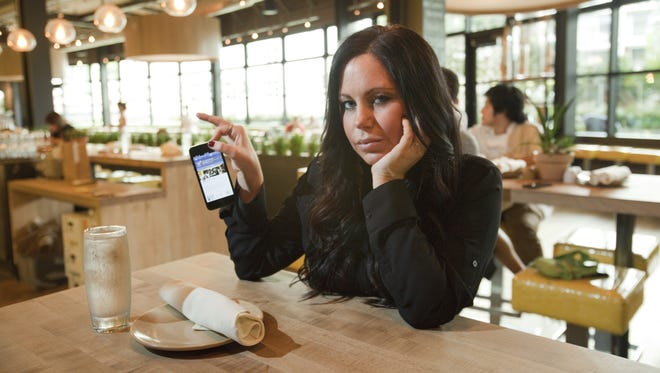 Brittany Morton, 27, photographed holding her iPhone at True Food Kitchen in Santa Monica, California, thinks it's rude if her boyfriend whips out his smartphone over dinner. Imagine what she will think when it is attached to his face as computerized glasses or strapped to his wrist, stealing his attention at every glance.