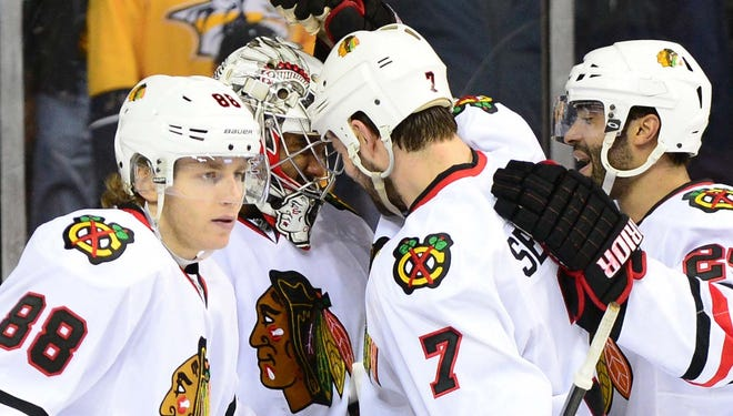 The Blackhawks congratulate Ray Emery, center, on his second shutout of the season.