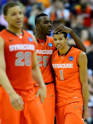 Syracuse Orange guard Michael Carter-Williams (1) and forward Rakeem Christmas (25) react after defeating the Marquette Golden Eagles during the finals of the East regional of the NCAA tournament at the Verizon Center. Syracuse won 55-39.