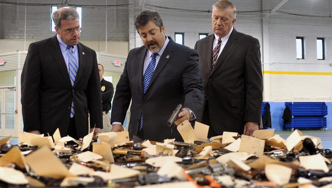 From left, N.J. Attorney General Jeff Chiesa, Atlantic County Chief of Detectives Daren Dooley, and and interim Atlantic County Prosecutor James McClain, look over the thousands of guns recovered during a weekend buyback at the Atlantic City Armory, in Atlantic City, N.J., on March 25.