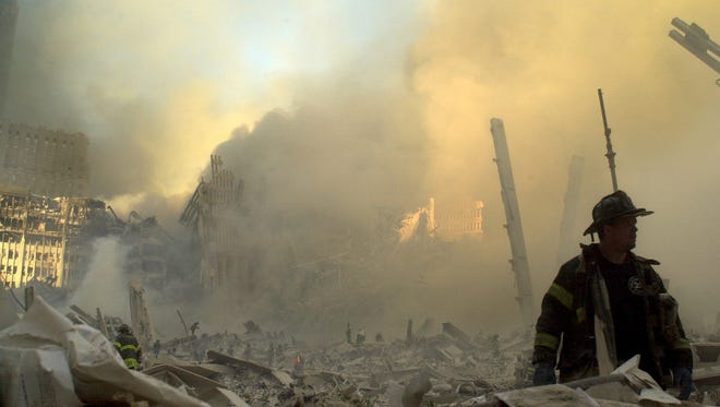 A firefighter moves through piles of debris at the site of the World Trade Center in New York on Sept. 11, 2001.