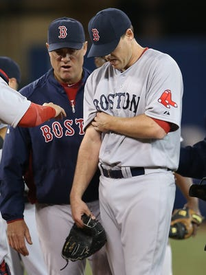 John Lackey leaves the game in the fifth inning due to an injury to his pitching arm.