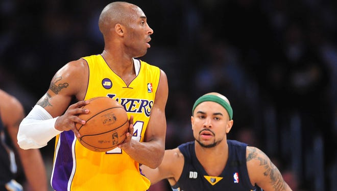 Los Angeles Lakers shooting guard Kobe Bryant (24) controls the ball against the defense of Memphis Grizzlies point guard Jerryd Bayless (7) during the first half at Staples Center.