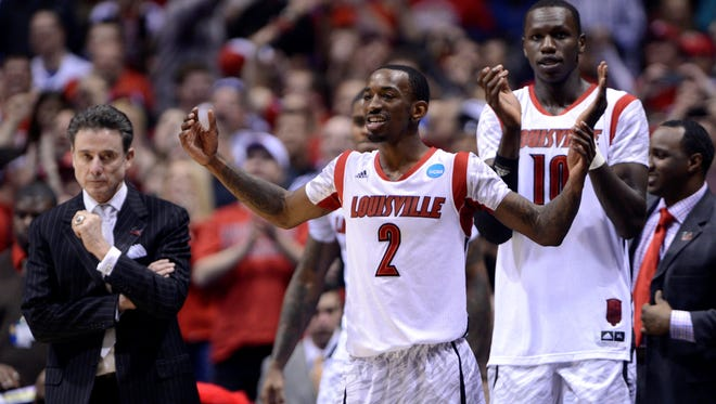 Louisville Cardinals head coach Rick Pitino and players Russ Smith and Gorgui Dieng celebrate from the bench in the second half of the Midwest regional against the Duke Blue Devils at Lucas Oil Stadium.