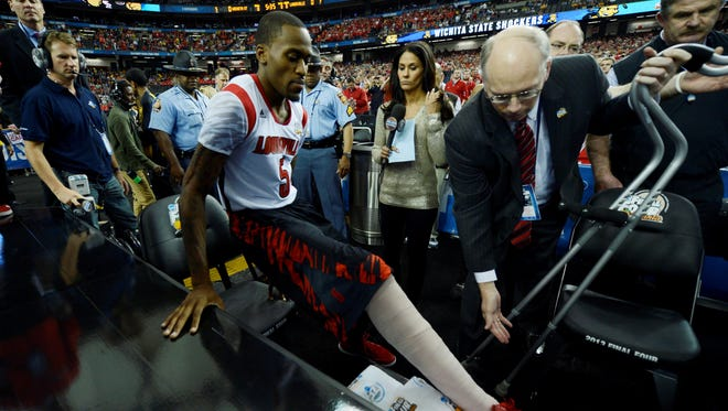 Louisville guard Kevin Ware (5) eases into his seat by the Cardinals' bench as  associate athletic director Kenny Klein handles Ware's crutches before tipoff of Louisville's national semifinal against Wichita State at the Georgia Dome.