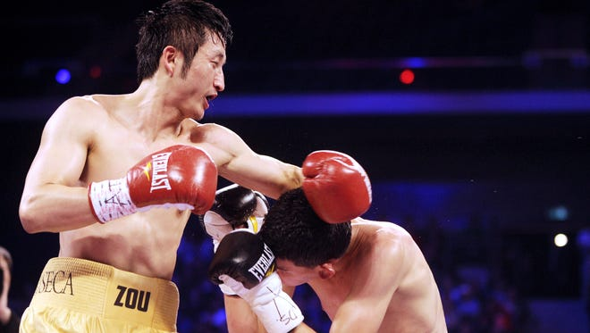 China's Zou Shiming, left, competes against Mexico's Eleazar Valenzuela during their flyweight bout at the 'Fists of Gold' boxing event in Macau on Saturday. Zou won a four-round decision, dominating the fight.