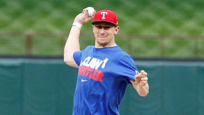 Texas A&M quarterback Johnny Manziel throws out the first pitch before the Rangers-Angels game Sunday.