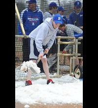 With temperatures hovering in the 30's, Brainerd High School sophomore  baseball player Matt Schubert shovels snow away from the batting cage on the high school baseball field Monday April 8, 2013 in Brainerd MN. The batting cage was still surrounded by snow after the school district used snowblowers to remove snow from the field last week in preparation for Tuesday's, April 9th's game, which has now been postponed because of cold weather.  (AP Photo/Brainerddispatch, Steve Kohls) ORG XMIT: MNBRA101