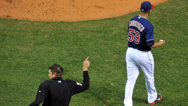 MLB umpire Jordan Baker (71) ejects Cleveland Indians starting pitcher Carlos Carrasco (59) after he hit third baseman Kevin Youkilis (36) with a pitch in the fourth inning at Progressive Field.