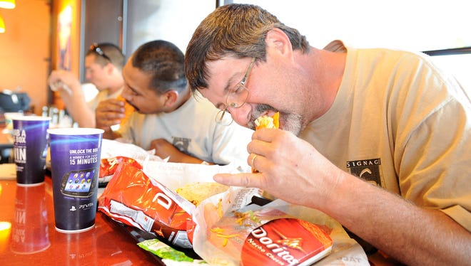 Customers enjoy the Doritos Tacos at  a Taco Bell in Lake Forest, Calif.