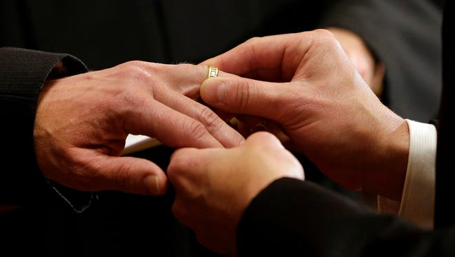 Thomas Rabe, right, places a wedding ring on Robert Coffman's finger during a marriage ceremony at City Hall in Baltimore earlier this year.