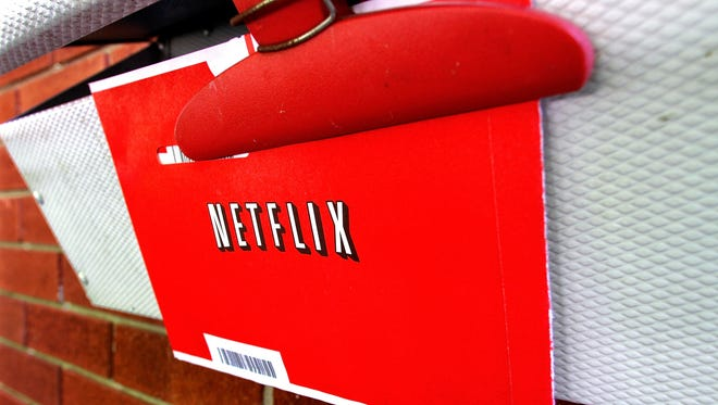 A Netflix envelop containing a DVD to be returned by mail is clipped onto a mailbox.