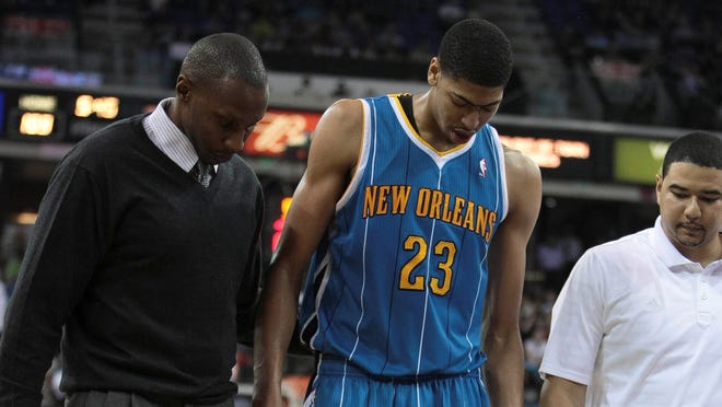 Anthony Davis leaves the court with the help of trainers.