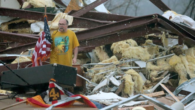Benjamin Pierce, a patron of the Botkinburg Foursquare church, sifts through the wreckage of the church after a storm demolished it Wednesday just north of Clinton, Ark.