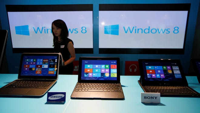 A woman walks past laptop computers running Microsoft Windows 8 operating system during its launching ceremony in Hong Kong.