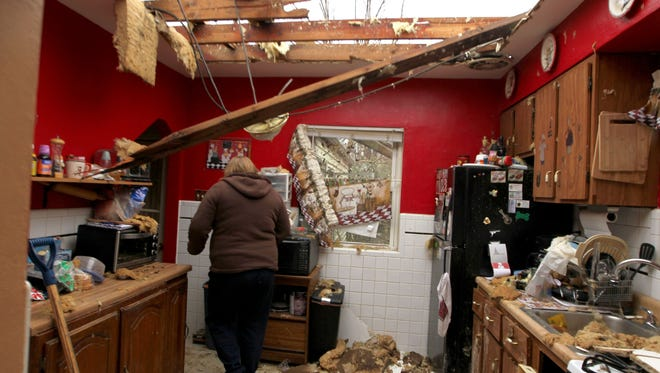 Karla Buneta walks through her storm-damaged kitchen in her home Thursday in Hazelwood, Mo. The National Weather Service says a tornado is believed to have been the culprit that damaged dozens of homes in the St. Louis suburb of Hazelwood.