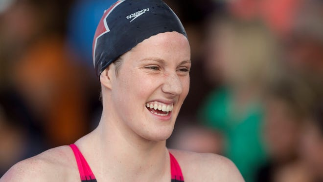 Missy Franklin heads past fans laughing after winning the championship final of the 100 meter freestyle during the Arena Grand Prix swim meet at the Skyline Aquatic Center in Mesa, Ariz.