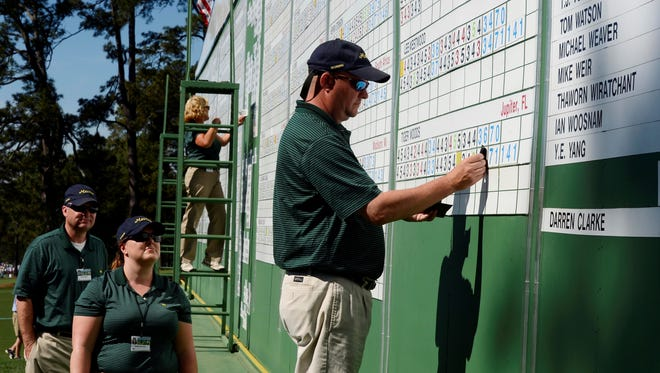 Phillip Hodges of Augusta changes Tiger Woods' score to reflect the two-shot penalty he was given Saturday morning.