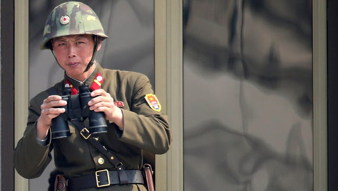 A North Korean soldier watches the South Korean side at the border village of Panmunjom in the Demilitarized Zone on April 4.