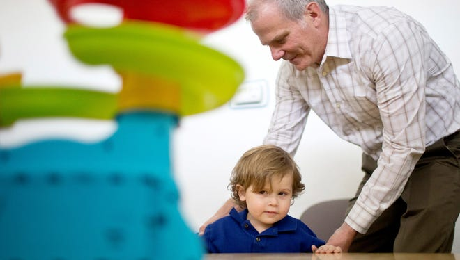 Dr. Chris Smith works with 2-year-old Blake Allen at the Southwest Autism Research and Resource Center in Phoenix.