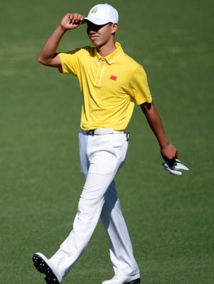 Guan Tianlang acknowledges the crowd at Augusta.