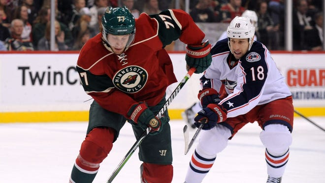 Columbus Blue Jackets forward RJ Umberger (18) defends Minnesota Wild defenseman Tom Gilbert (77) during the first period at the Xcel Energy Center.
