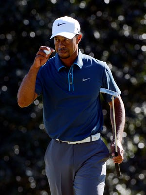 Tiger Woods reacts after making his putt on the 14th green.