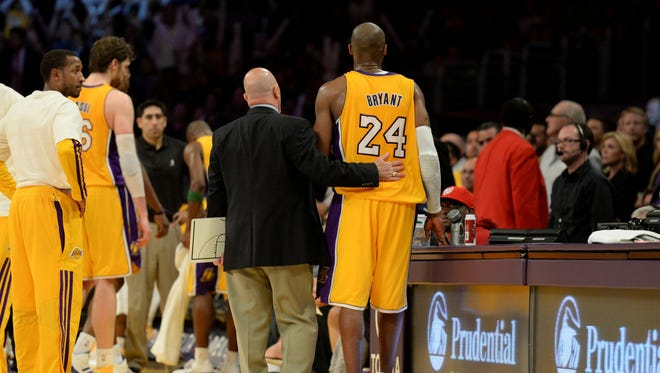 Lakers guard Kobe Bryant walks gingerly off the court after injuring his foot Friday vs. the Warriors.