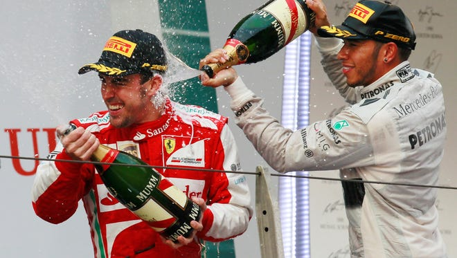 Ferrari driver Fernando Alonso is sprayed with champagne by second placed Mercedes driver Lewis Hamilton of Britain after winning the Chinese Formula One Grand Prix in Shanghai, China.