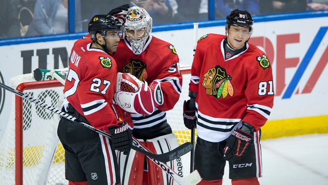Chicago Blackhawks goalie Corey Crawford is congratulated by teammates  Johnny Oduya, left, and Marian Hossa after he shuts out the St. Louis Blues.