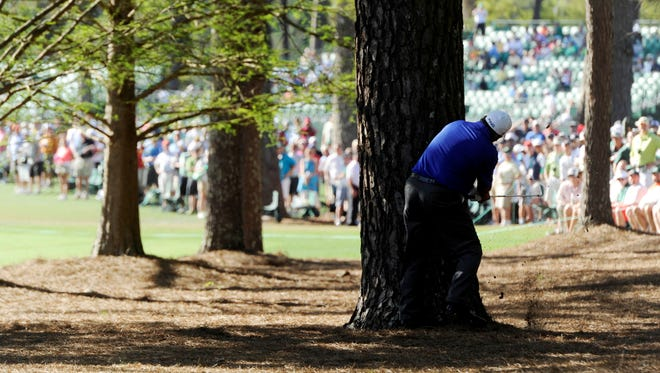Angel Cabrera plays a shot from out of the rough and behind a tree on the 13th hole during the third round of the Masters in Augusta, Ga. Cabrera shot a 3-under 69 on the day and is tied for the lead heading into the final round at Augusta National.