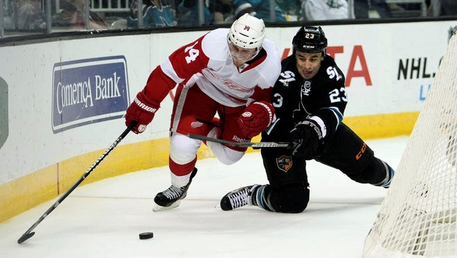 Red Wings forward Gustav Nyquist, left, battles Sharks center Scott Gomez for the puck during a game last month.