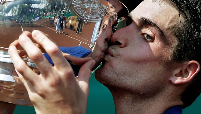 John Isner kisses the trophy after his 6-3, 7-5 win after defeating Nicolas Almagro in the U.S. Men's Clay Court Championship final.