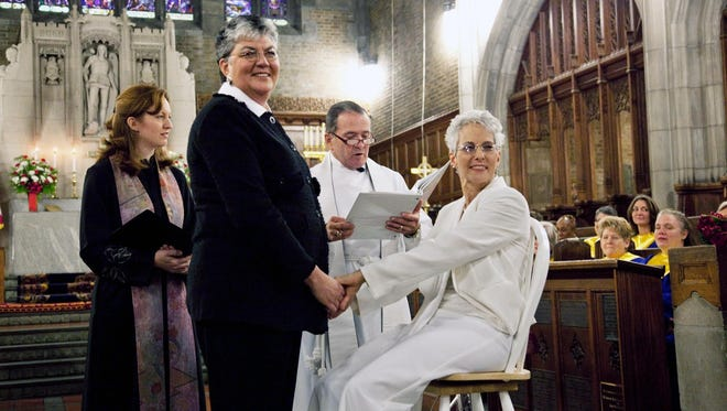 Sue Fulton, left, and Penelope Gnesin exchange wedding vows at West Point's Cadet Chapel in December.