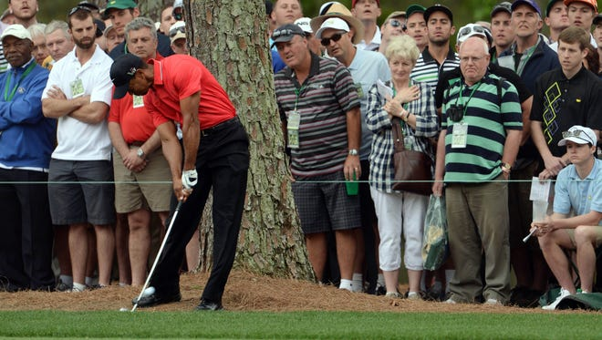 Tiger Woods hits out of the rough next to a tree on the first hole during Sunday's final round of the Masters