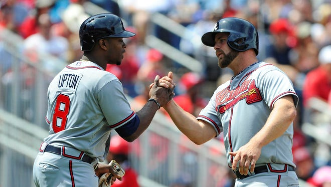 Justin Upton and catcher Evan Gattis celebrate after scoring runs during the first inning Sunday.