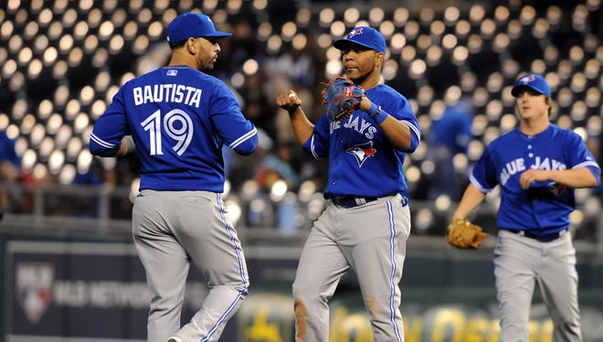 Jose Bautista, here celebrating with first baseman Edwin Encarnacion, has played two games at third since Jose Reyes got injured, and may stick there a while.