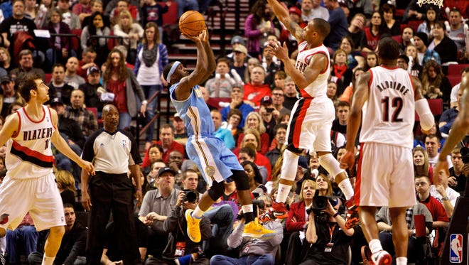 Feb 27, 2013; Portland, OR, USA; Denver Nuggets point guard Ty Lawson (3) shoots over Portland Trail Blazers point guard Damian Lillard (0) at the Rose Garden.