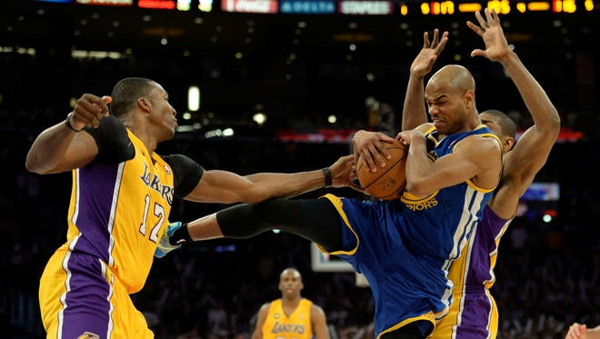 Warriors guard Jarrett Jack pulls down a rebound in front of Lakers forward Metta World Peace and Dwight Howard during Friday's 118-116 loss.