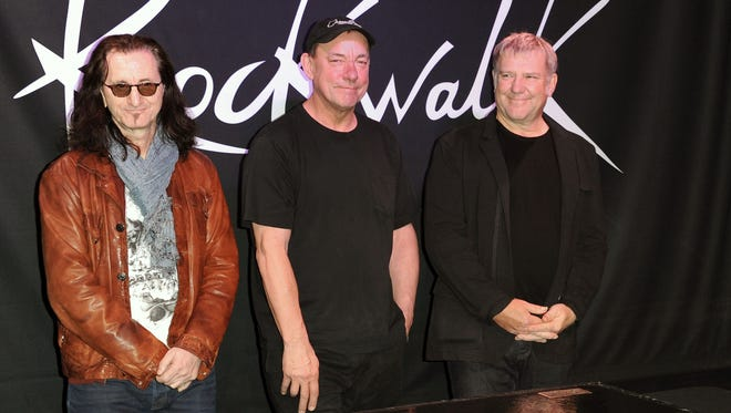 This Nov. 20, 2012 file photo shows members of the band Rush, from left, Geddy Lee, Neil Peart and Alex Lifeson, at the RockWalk induction of Rush at Guitar Center in Los Angeles.