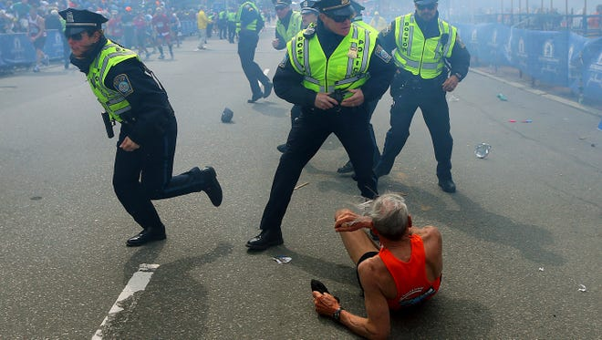Police officers react to a second explosion at the finish line of the Boston Marathon Monday. The runner has been identified as Bill Iffrig, 78, of Lake Stevens, Wash. He was not seriously injured.