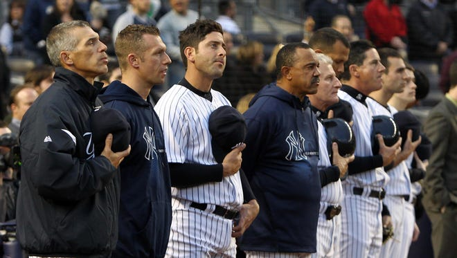 New York Yankees players and coaches stand during the national anthem before the game against the Arizona Diamondbacks at Yankee Stadium.