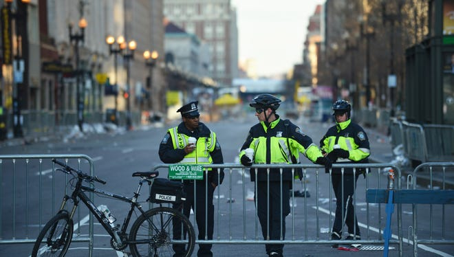 Boston police officers stand at barriers closing off Boylston Street today in the aftermath of two explosions that struck near the finish line of the Boston Marathon.