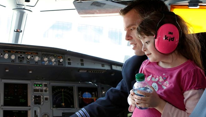 Rebekah Tirrell, of Johnston, R.I., receives a flight lesson from Jonathan Wakeman, first officer at JetBlue, during 'Wings For Autism' program at Boston Logan Airport on April 6.