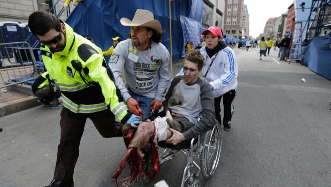 Medical workers move an injured man past the finish line at the 2013 Boston Marathon following an explosion on Monday.
