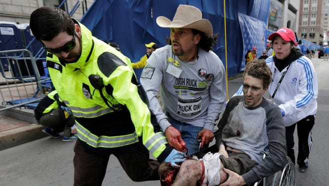 Medical responders run an injured man past the finish line at the Boston Marathon following an explosion in downtown. Two explosions shattered the euphoria of the Boston Marathon finish line, sending authorities out on the course to carry off the injured while the slower runners were rerouted away from the smoking site of the blasts.