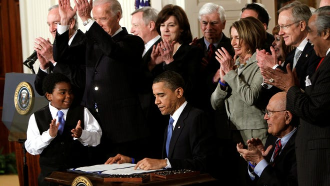 President Obama is applauded after signing the Affordable Care Act into law on March 23, 2010.