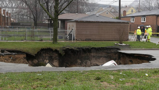Officials survey a gaping sinkhole that opened up a residential street in Chicago on Thursday.