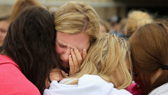 West High School senior Mackenzie Wernet is embraced by fellow students after praying for the victims and survivors the day after the West Fertilizer Company explosion April 18, 2013, in West, Texas. Wernet's home was destroyed.