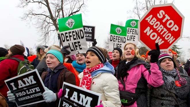 Anti-abortion activists march past the  Supreme Court in January.